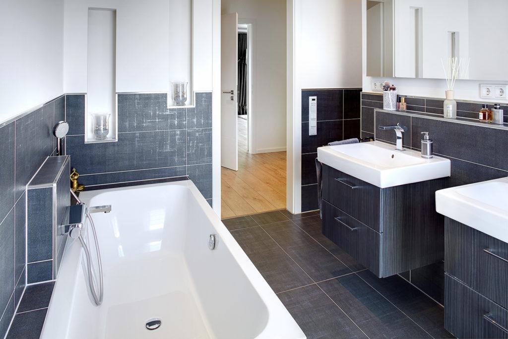 Rechteckwanne in einem grau-gefliesten Badezimmer
