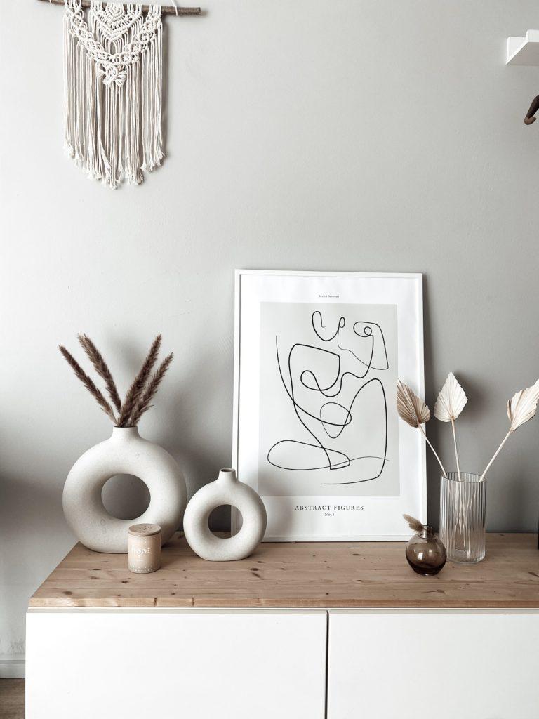 Desenio Poster mit abstrakter Figur auf Sideboard